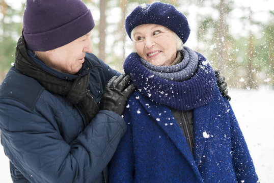 two older adults in the snow