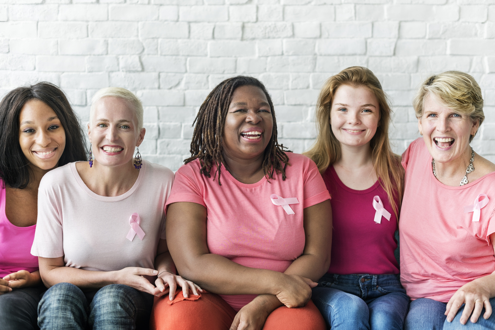 diverse group of women wearing tshirts that are various shades of pink with breast cancer awareness ribbons