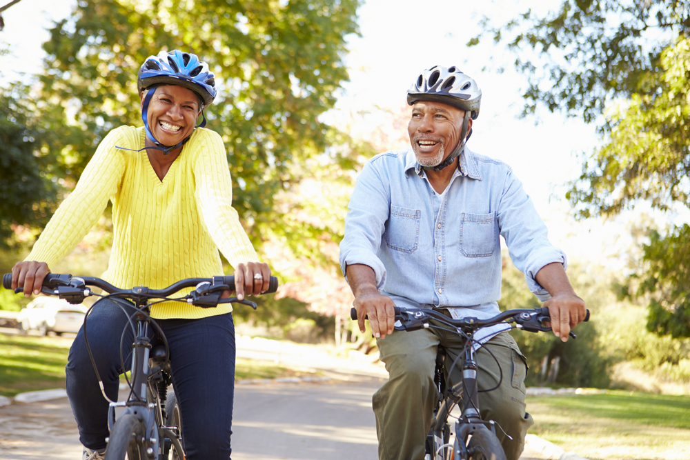 African american man and woman riding bicycles and helmuts