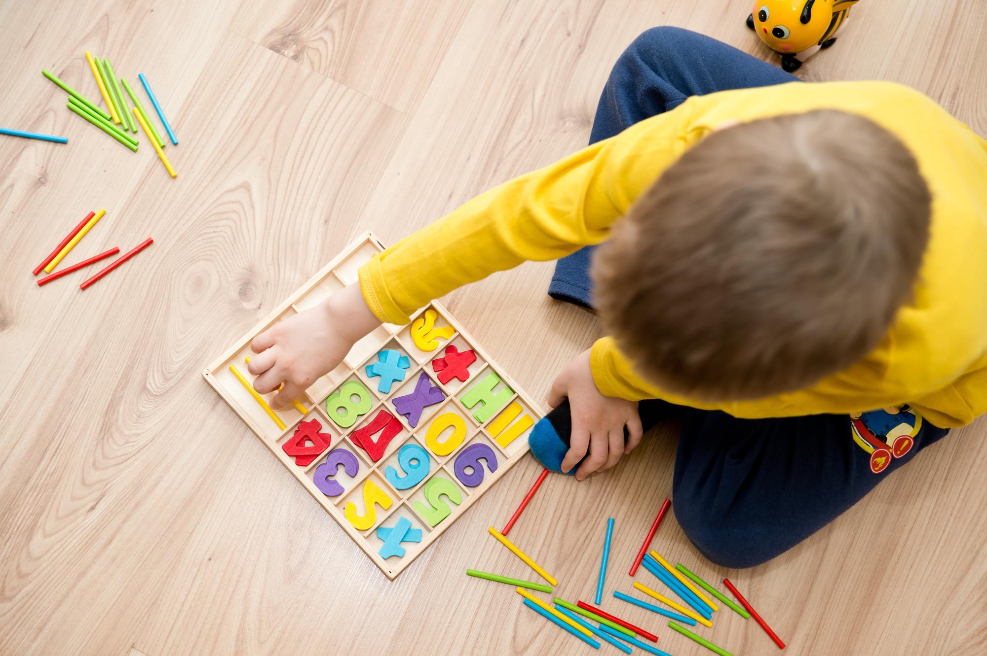 Un niño pequeño que juega con un sistema de conteo coloreado en el suelo.