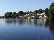 View from a dock looking across a bay. Houses line the shore on the left side of the image.