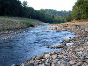The Patapsco River flows through the valley. Rocks line the shore. Fishermen are barely visible.