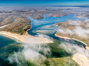 Aerial view of a river and estuary surrounded by mountainous terrain.