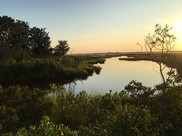 The sun heads down above a Maryland marsh, the blue sky reflecting off the still water.