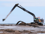 A large excavator machine moves sediment on Queen Bess Island.