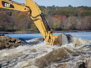 Construction equipment removing debris from a river