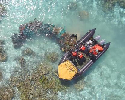 Marine debris team hauling derelict net.