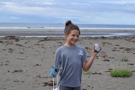 Million Waves Project prosthetic hand recipient, picks up debris.