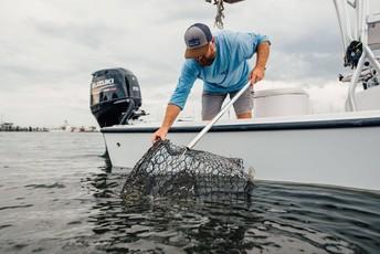 Volunteer removing derelict crab pot from ocean.