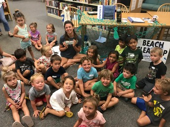 Surfrider volunteer and children at a Whales at Your Library event.