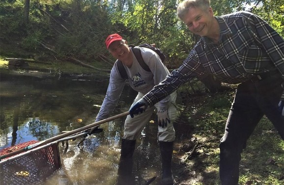 Two volunteers removing debris from a river during a cleanup.