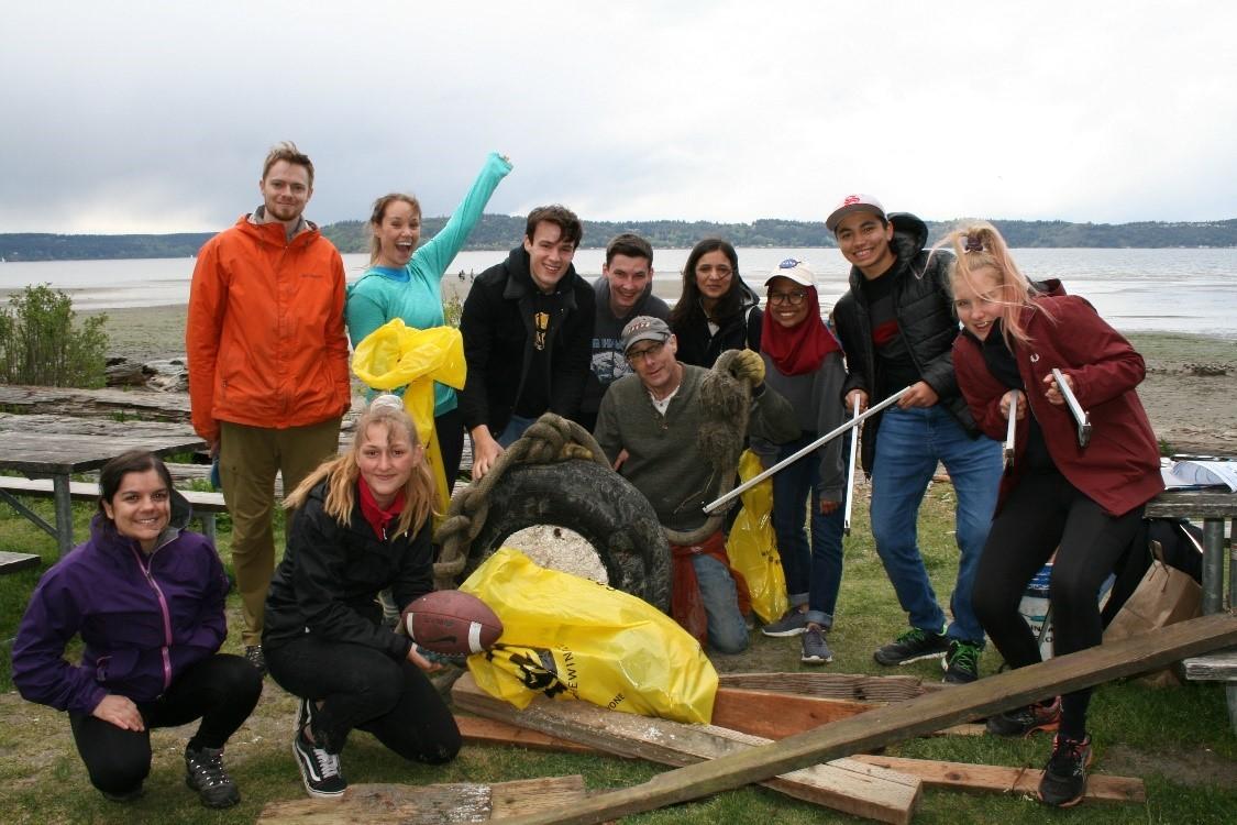 Beach cleanup volunteers pose next to their marine debris haul.