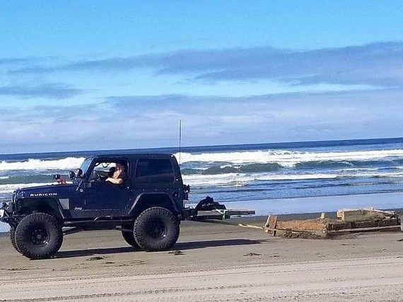 A Jeep hauling a large piece of an old dock from the beach.