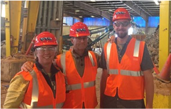 Three people at an industrial wast processing and recycling facility.