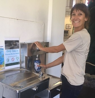 An event goer uses a newly installed water bottle refilling station.