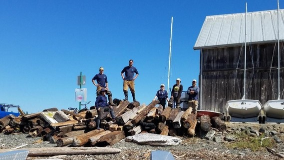 The EarthCorps crew poses on a pile of marine debris cleaned up in one week.