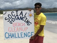 Two volunteers posing with social distancing beach cleanup sign on a beach.