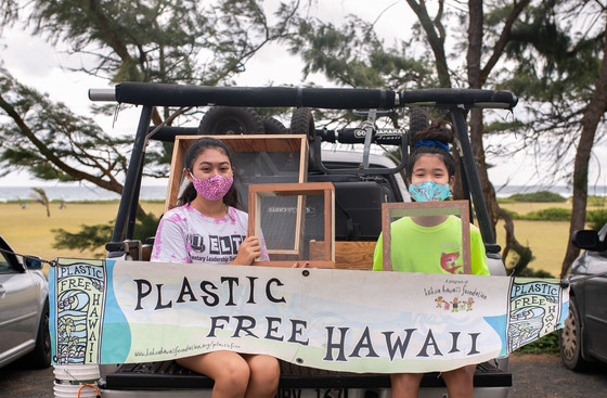 Girl Scouts hold up a Plastic Free Hawaii banner.