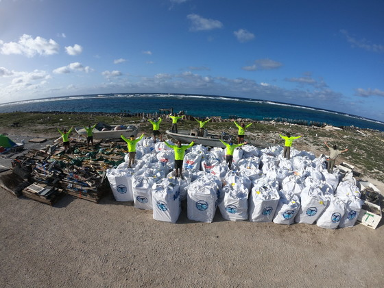 A marine debris removal team stand atop 82,600 pounds of collected marine debris.