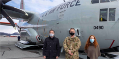 People wearing masks standing in front of a military plane