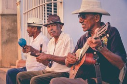 Image shows three, older Cuban men playing instruments