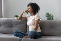 Image shows a young Black woman in thought