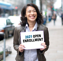 """Image shows a woman holding a sign that reads, """"2021 Open Enrollment."""""""