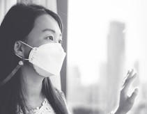 Image shows a young Asian woman wearing a facemask