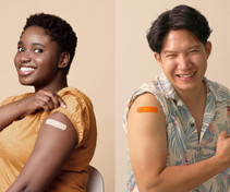 Image shows a Black woman and an Asian man who have received their vaccine shot