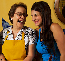 Image shows tow Latina women talking and laughing