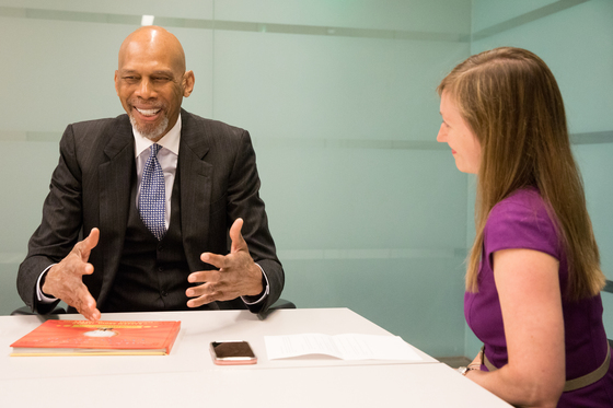 Kareem Abdul-Jabbar sits across from female interviewer smiling and gesturing with his hands.