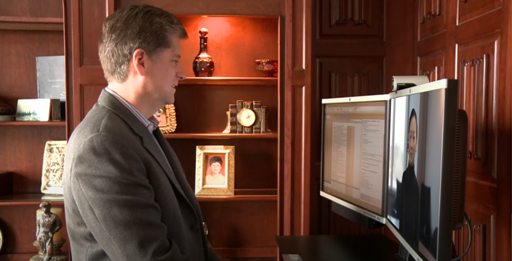 A man conducts an interview with a woman on a computer screen.