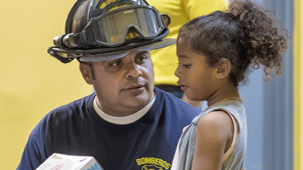 Picture of a firefighter talking to a little girl.