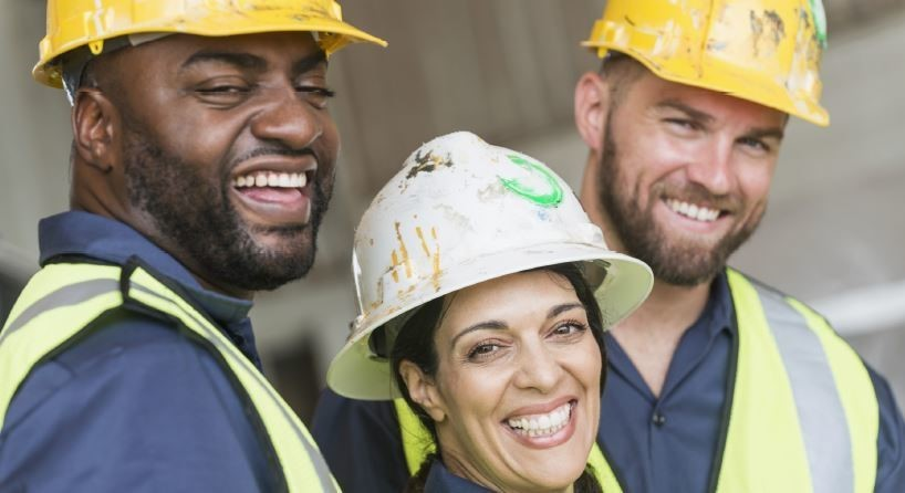 Two men and one woman, all in construction hard hats, smiling together.