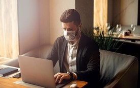 Business owner at computer with mask on.