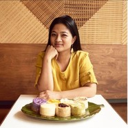 Photo of a woman in front of a table with a plate of cheesecakes