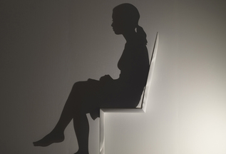 Shadow silhouette of a woman sitting in a white chair