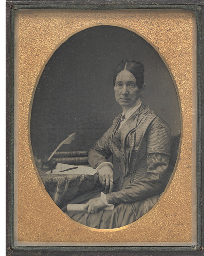 Black and white photo of woman sitting at desk holding scroll