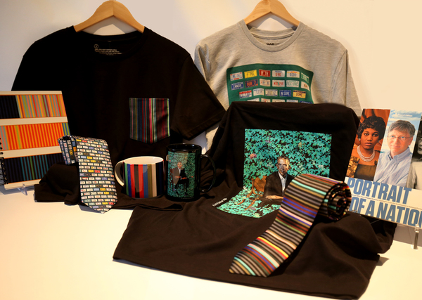 An array of t-shirts, mugs and ties with art products on them