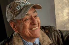 Photograph of a smiling Veteran wearing a baseball cap.