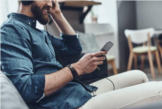 Man wearing headphones looking at his phone.