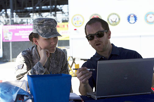 VA employee helping a Servicemember with a laptop.