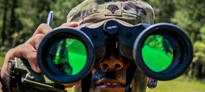 soldier looking through binoculars