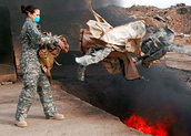 Female Service member discarding materials in a burn pit
