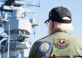 U.S. Veteran standing by a ship