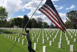 Young boy holding the U.S. flag in a VA national cemetery