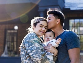 Service member hugs her child and husband