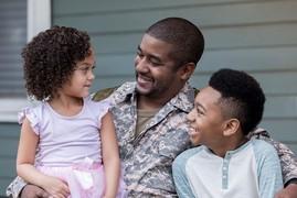Service member hugs his children
