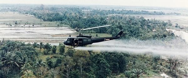 Helicopter distributing Agent Orange herbicide over forest in Vietnam