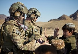 Service members receive high fives from children in Farah province, Afghanistan